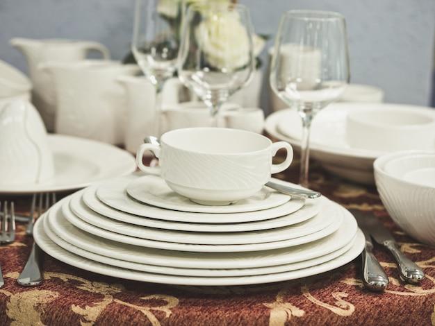 Set di nuovi piatti sul tavolo con tovaglia. pila di piatti bianchi e bicchieri di vino con fiori sul tavolo del ristorante. dof poco profondo Foto Premium