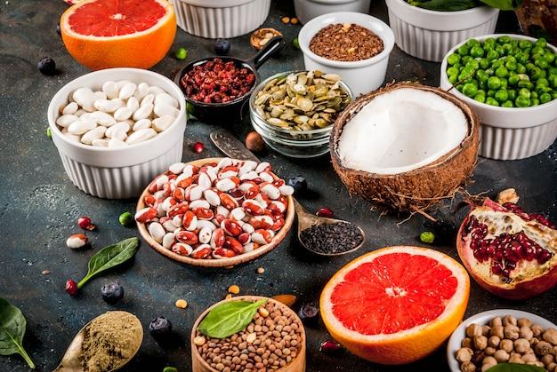 Set di alimenti biologici sani, fagioli superfood, legumi, noci, semi, verdure, frutta e verdura. blu scuro Foto Premium