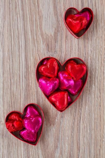 Set di caramelle cuore rosso e rosa sulla tavola di legno Foto Premium