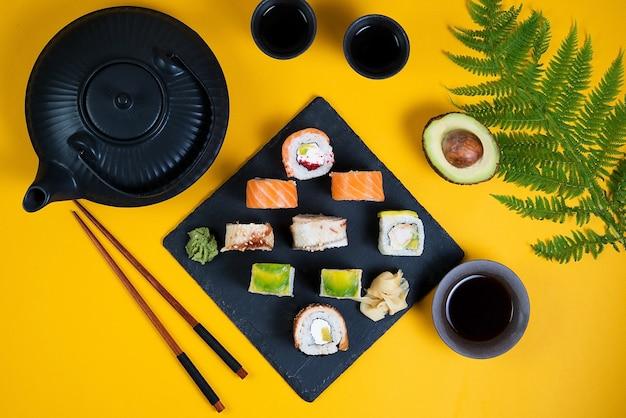 Un set di sushi roll tipo diverso su uno spazio giallo. vista dall'alto. cibo asiatico tradizionale Foto Premium