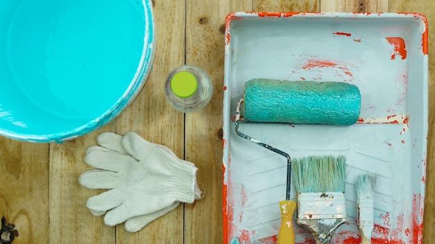 Set di strumenti per dipingere la parete su uno sfondo di legno a casa. Foto Premium