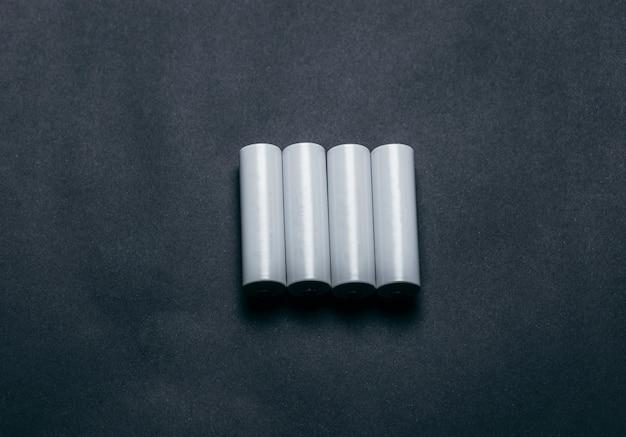 Diverse batterie aa bianche vuote su spazio carta nera Foto Premium