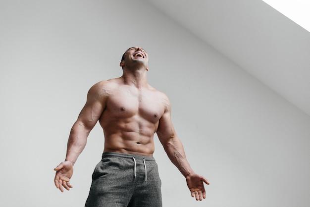 Atleta sexy in posa su uno sfondo bianco in topless. fitness Foto Premium