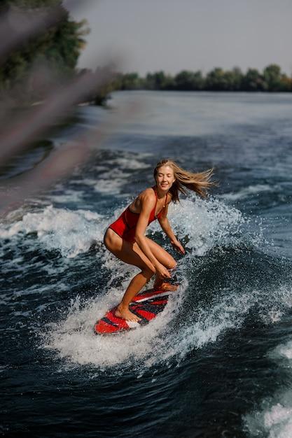 Donna bionda sexy che pratica il surfing a bordo giù l'acqua blu Foto Premium