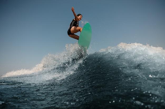 Donna sexy del brunette che salta su un wakeboard sull'alta onda blu Foto Premium