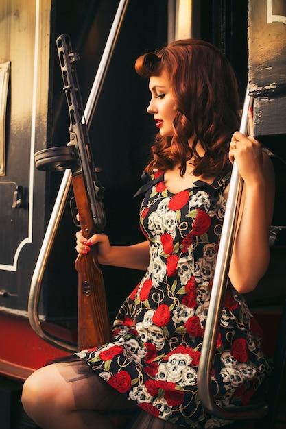 Donna castana sexy in stile pin up retrò vicino al vecchio treno. tiene il fucile Foto Premium