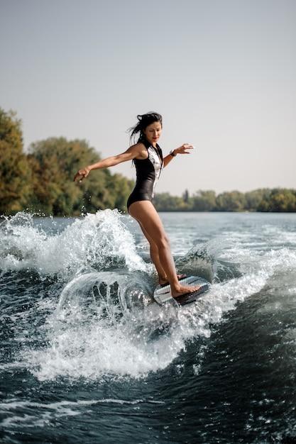 Donna sexy del brunette che pratica il surfing a bordo giù l'acqua blu Foto Premium