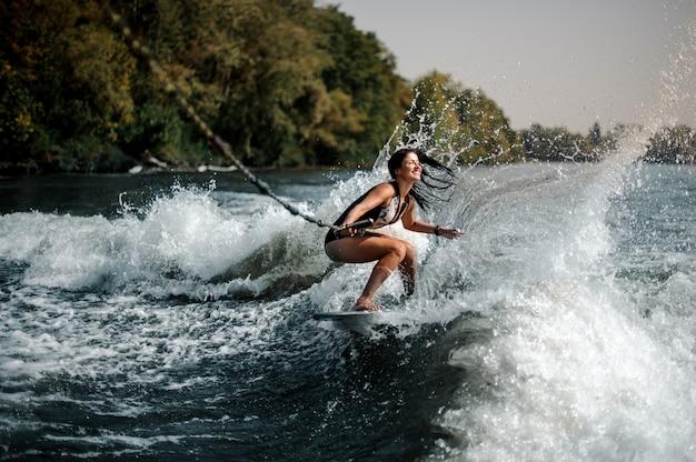 Donna sorridente sexy del brunette che pratica il surfing a bordo giù l'acqua blu Foto Premium