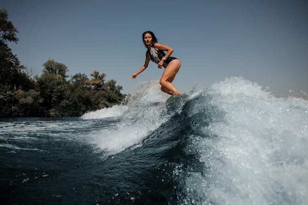Giovane donna sexy del brunette che pratica il surfing a bordo giù l'acqua blu Foto Premium