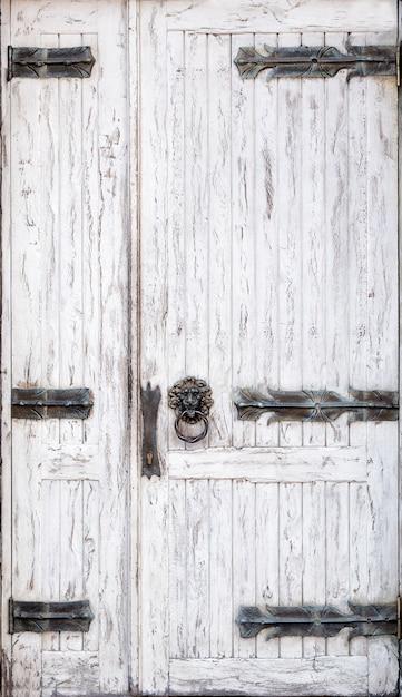 Porta in legno bianco squallido con cerniere forgiate e una maniglia a forma di anello a forma di testa di leone Foto Premium