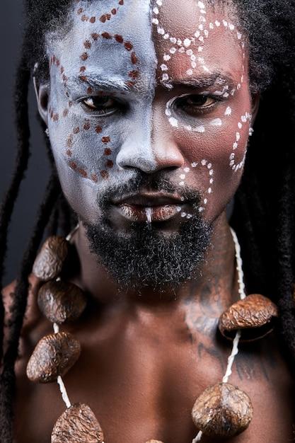 Uomo rituale tribale sciamano isolato in studio, aborigeno esotico con trucco etnico sul viso, maschio africano senza camicia con i dreadlocks Foto Premium