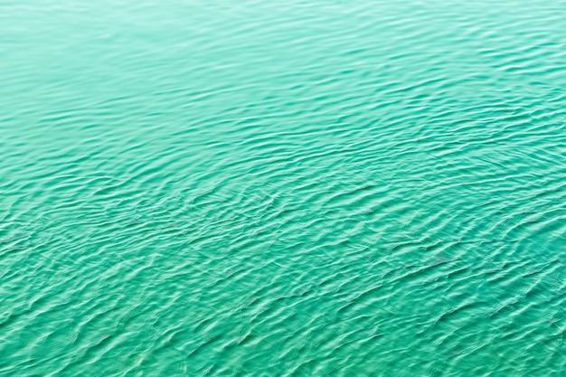 Fondo ondulato verde brillante dell'ondulazione della superficie dell'acqua Foto Premium
