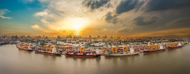 Porto di spedizione in riva al fiume in città sul tramonto preso da drone Foto Premium