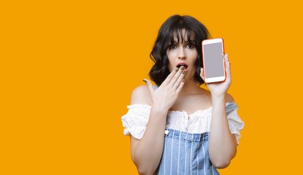Signora caucasica scioccata con i capelli neri che mostra il suo telefono mentre posa su un muro giallo con uno spazio vuoto Foto Premium