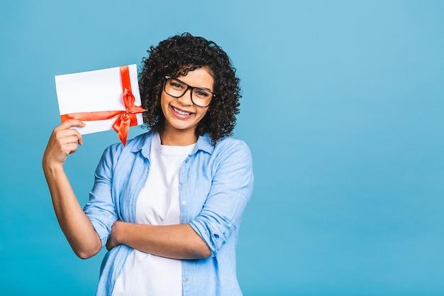 Giovane donna afroamericana riccia sorpresa scioccata isolata sul ritratto blu dello studio del fondo. mock up copia spazio. tenendo il buono regalo. Foto Premium