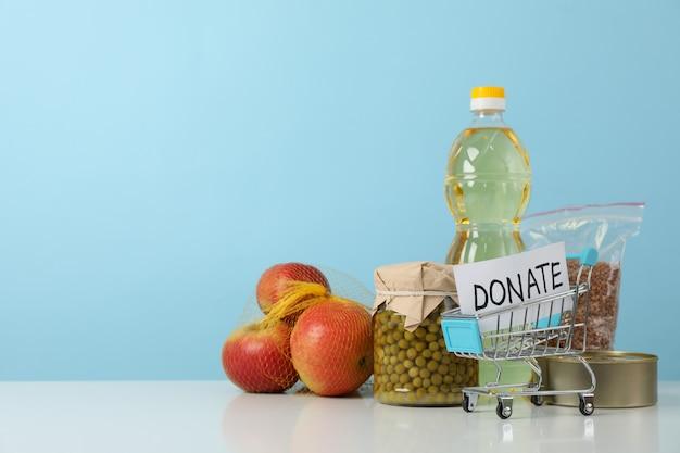 Carrello del negozio con il testo dona e cibo diverso contro lo spazio blu Foto Premium