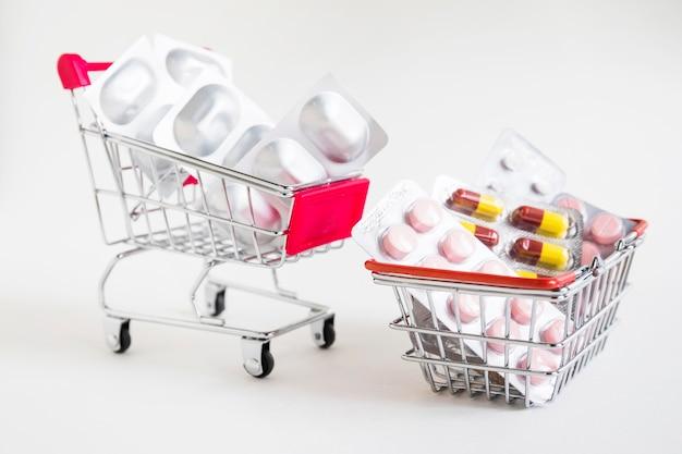 Carrelli della spesa con le medicine della bolla su fondo bianco Foto Premium