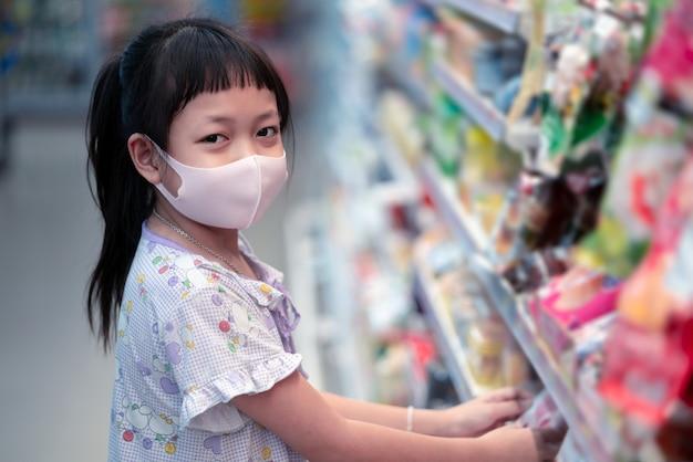 Concetto di acquisto con bambini asiatici durante l'epidemia di virus. frutta d'acquisto da portare della maschera di protezione del bambino in supermercato nella pandemia del coronavirus. Foto Premium