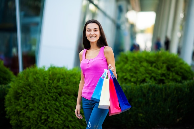 Giornata di shopping. sacchetti colorati della holding della donna vicino al suo centro commerciale shooping nella festa nera di venerdì. Foto Premium