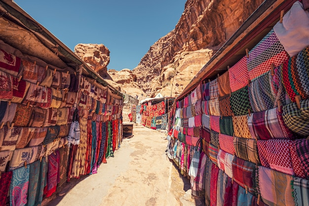 Via dello shopping con mercato nell'antica città di petra in giordania con prodotti souvenir, tessuti e tappeti con ornamenti beduini nazionali Foto Premium