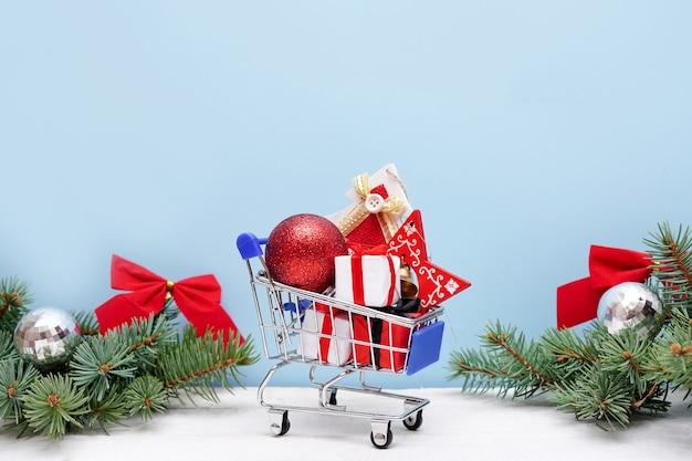 Carrello della spesa con scatole regalo di natale e decorazioni su sfondo blu. saldi di natale e capodanno. Foto Premium