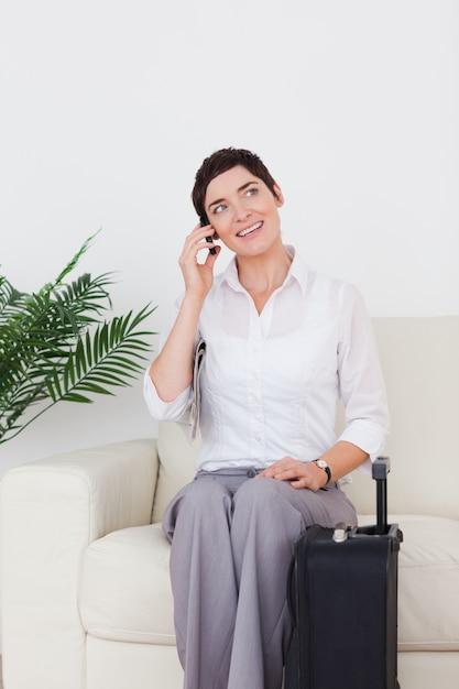 Donna dai capelli corti al telefono con una valigia | Foto ...
