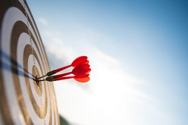 Sparato frecce rosse delle frecce nel centro dell'obiettivo sulla parete del cielo blu Foto Premium