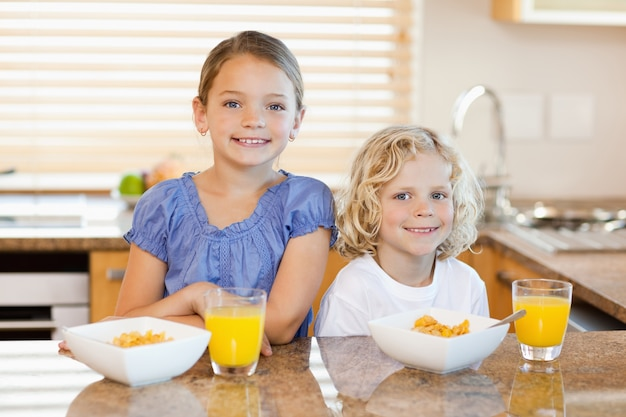 Fratelli germani con colazione dietro il bancone della cucina Foto Premium