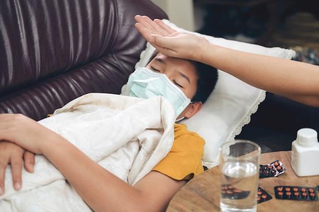 Bambino malato sdraiato nel divano letto con maschera di protezione sul viso contro l'infezione Foto Premium