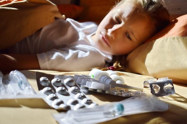Ragazza malata del bambino a letto con le medicine. raffreddori stagionali nei bambini. malattie dei bambini trattamento domiciliare per un bambino. bebè e pillole. Foto Premium