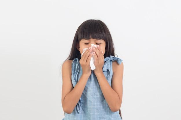 Bambina ammalata che soffia il naso isolato su bianco Foto Premium