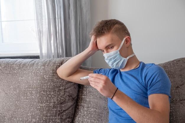 Uomo malato che si siede sul sofà e che controlla la sua temperatura con il termometro a casa. Foto Premium