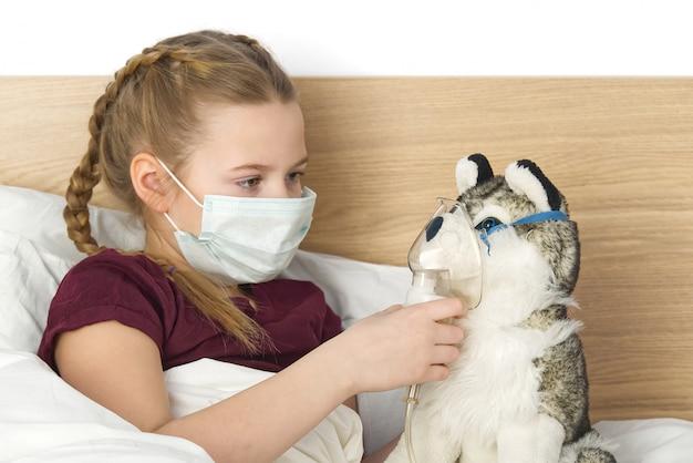 Bambino triste malato in una maschera con una temperatura e un mal di testa giace nel letto. Foto Premium