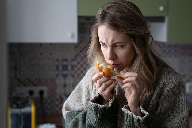 Una donna malata che cerca di percepire l'odore di arancia mandarino fresca, ha sintomi di covid-19, virus corona Foto Premium