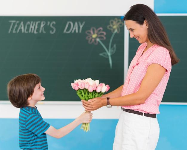 Ragazzo di vista laterale che dà un mazzo di fiori al suo insegnante Foto Premium