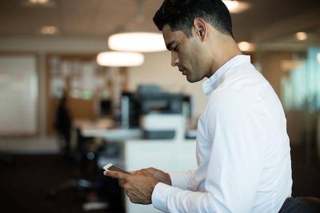 Vista laterale dell'uomo d'affari utilizzando il telefono cellulare Foto Premium