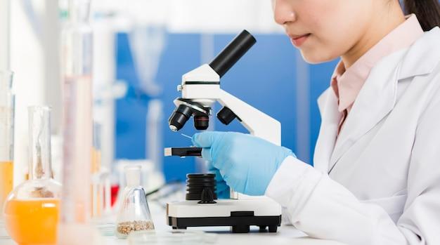 Vista laterale della scienziata con i guanti chirurgici che guardano tramite il microscopio Foto Premium
