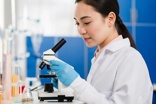 Vista laterale della scienziata con guanti chirurgici e microscopio Foto Premium
