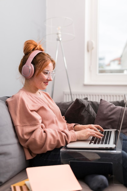 Vista laterale dell'insegnante femminile utilizzando laptop e cuffie da casa per la lezione online Foto Premium