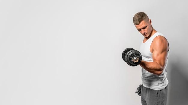 Vista laterale dell'uomo in forma con canotta utilizzando i pesi Foto Premium