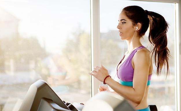 Vista laterale della ragazza di forma fisica giovane e persistente attraente concentrata che pratica sul tapis roulant nella moderna palestra soleggiata vicino alla finestra accanto a lei. Foto Premium