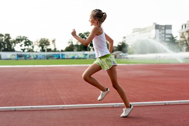 Vista laterale della ragazza sulla pista di atletica Foto Premium