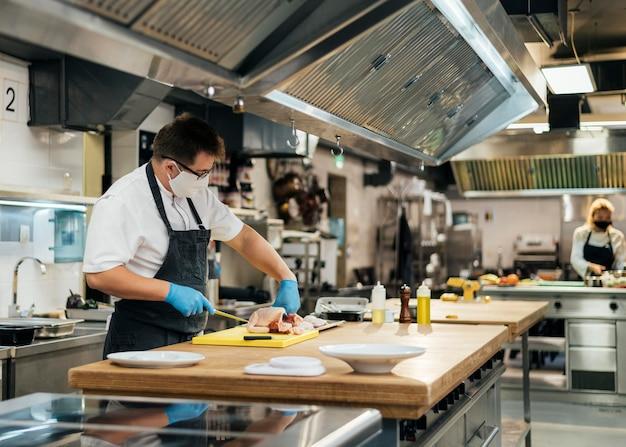 Vista laterale del cuoco unico maschio che cucina con mascherina medica in cucina Foto Premium