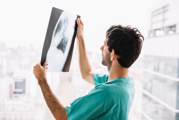 Vista laterale di un medico maschio guardando ai raggi x Foto Premium