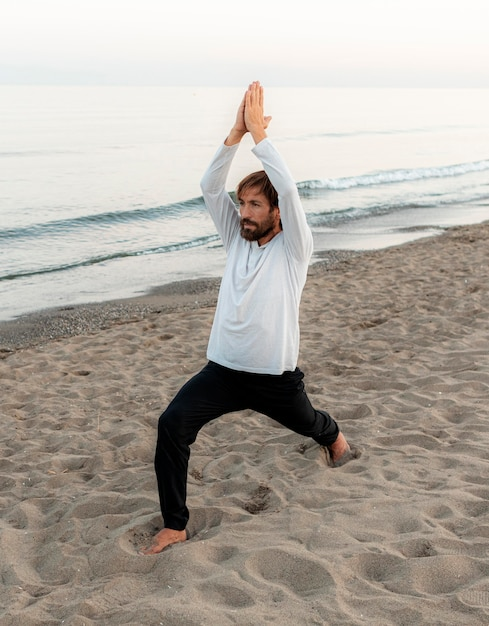 Vista laterale dell'uomo che fa yoga sulla spiaggia Foto Premium