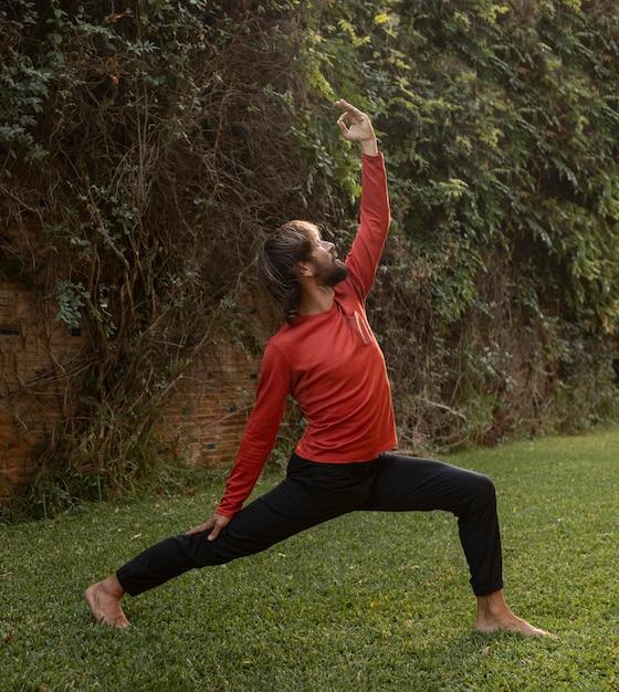 Vista laterale dell'uomo sull'erba che fa yoga Foto Premium