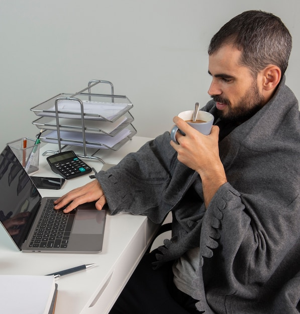 Vista laterale dell'uomo che mangia caffè mentre si lavora da casa Foto Premium