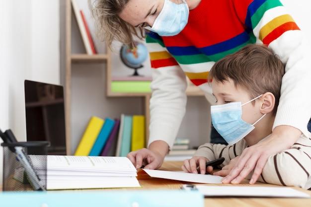 Vista laterale del figlio d'aiuto della madre con i compiti mentre indossando maschera medica Foto Premium