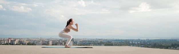Vista laterale della giovane donna muscolare con una lunga coda di cavallo nella mattina di sole Foto Premium