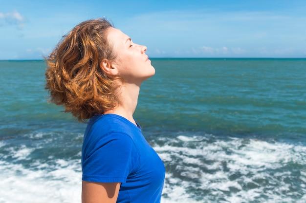 Vista laterale ritratto di donna rilassata respirando profondamente aria fresca su un mare Foto Premium